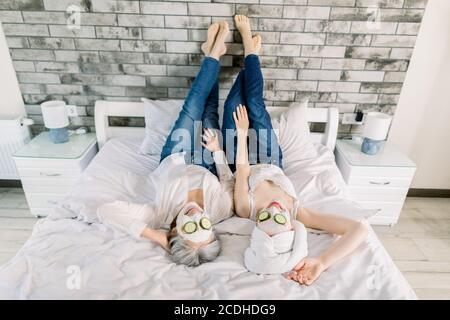 Vue de haut angle de deux femmes charmantes, femme sénior aux cheveux gris et jeune fille avec une serviette sur la tête, allongé sur le lit et profitant de la journée spa avec des masques de visage