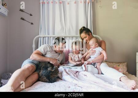 La famille s'asseyant ensemble sur le lit de bébé pendant qu'elle lit l'heure du coucher histoires