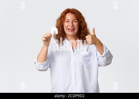 Louer, acheter des biens immobiliers et concept immobilier. Joyeuse et heureuse femme d'âge moyen à tête rouge montrant la carte de maison et les pouces vers le haut comme l'achat de la nouvelle maison