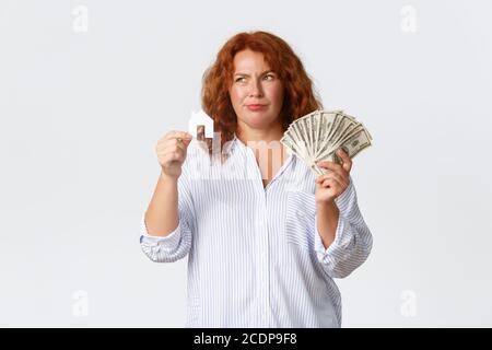 Louer, acheter des biens immobiliers et concept immobilier. Indécis et douteuse femme d'âge moyen hésitant avant d'acheter la maison, tenant la carte et l'argent à la maison