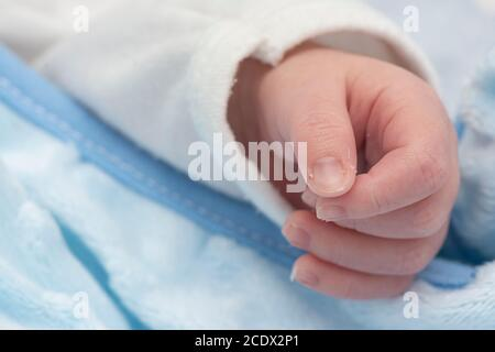 La main du nouveau-né dormait paisiblement au lit, photo macro