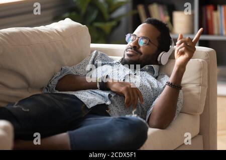 Homme afro-américain satisfait positif allongé sur un canapé, en appréciant la musique