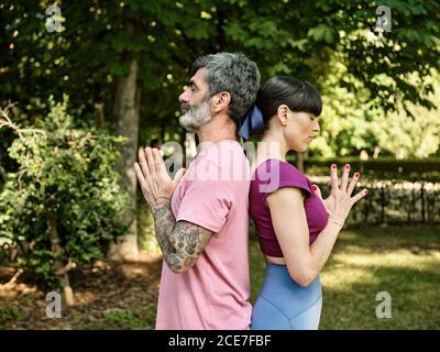 Vue latérale de l'homme et de la femme qui pratiquent le yoga Tadasana tout en se tenant dos à dos avec les yeux fermés et Namaste entre les mains dans le parc