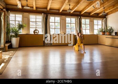 Femelle concentrée dans le long waving dressing se dressant pieds nus en studio et Pratiquer le yoga à Anjaneyasana