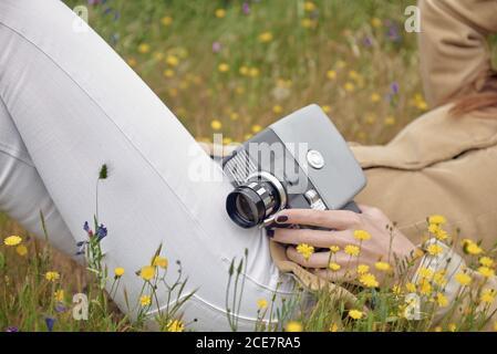 Vue latérale de la petite photographe anonyme en Jean couvrant faites face à un chapeau tout en étant allongé sur une prairie avec des fleurs colorées et en tenant votre ancienne caméra vidéo à la campagne Banque D'Images