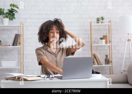 Problèmes de l'enseignement à distance. Une femme choquée tient la tête et regarde un ordinateur portable
