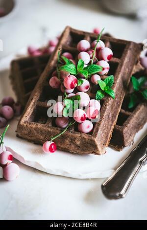 Des gaufres savoureuses au chocolat aux flocons d'avoine avec baies de gooseberries sont servies sur plaque blanche avec cuillère et couteau sur bois clair tableau