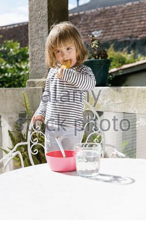 Enfant doux debout sur une chaise dans l'arrière-cour en été et manger un délicieux popsicle tout en regardant loin Banque D'Images