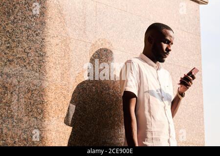 Jeune homme noir concentré en chemise blanche debout au mur à l'extérieur et en lisant des sms sur le téléphone ou en vérifiant le courrier