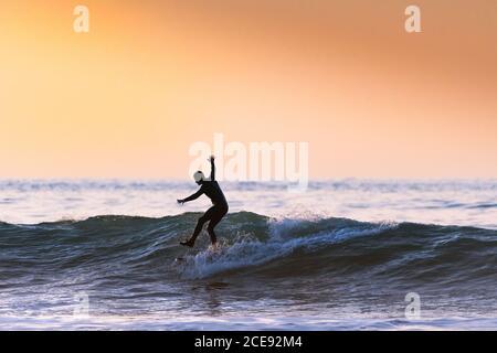 Un surfeur qui monte une vague et se tient sur une jambe en soirée à Fistral, à Newquay, en Cornwall.