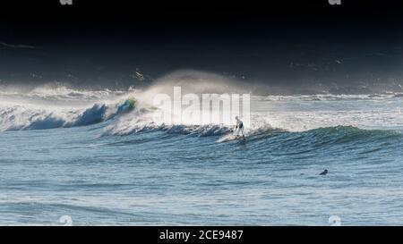 Une image panoramique d'un surfeur qui monte une vague à South Fistral à Newquay, en Cornwall.