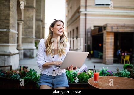 Heureuse femme excitée de lire de bonnes nouvelles en ligne dans un ordinateur portable en plein air Banque D'Images