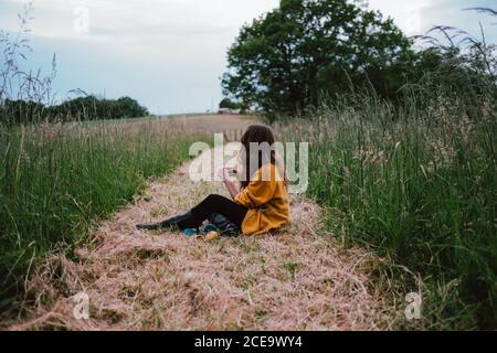 Vue latérale de la femme assise et se coince dans le champ. Prise de vue horizontale en extérieur.