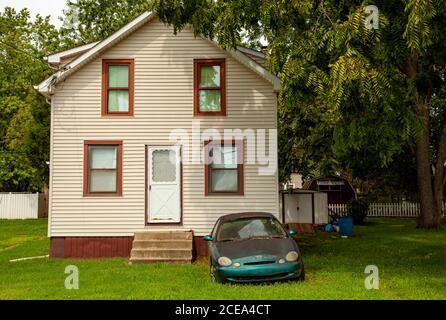 Chesapeake City, MD, Etats-Unis 08/25/2020: Une vieille voiture rouillée avec des phares brumeux est laissée devant une seule maison familiale avec une grande cour. C'est le cas Banque D'Images