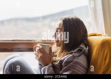 Vue latérale de la mignonne dans chaud pull souriant et dégustez une boisson chaude tout en étant assis dans un fauteuil près de l'immense fenêtre à la maison
