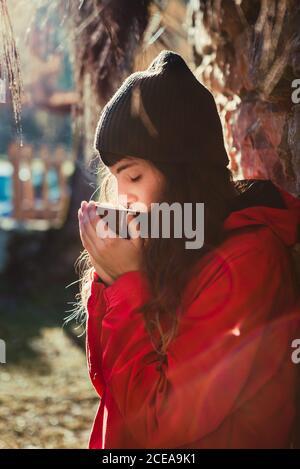 Vue latérale d'une jeune femme en tenue de chapeau élégante les yeux fermés et odeur de boisson chaude aromatique pendant que vous êtes assis campagne le jour ensoleillé