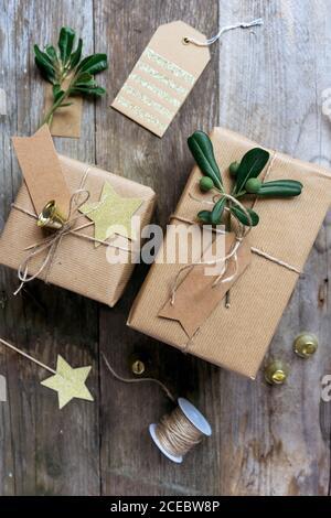Cadeaux faits maison emballés sur une table en bois avec des décorations de noël