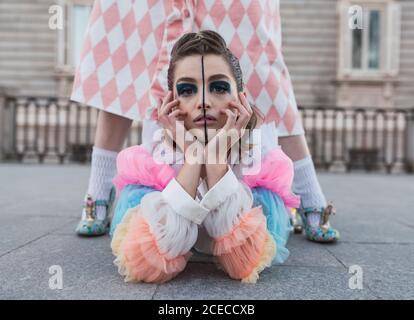 Jeune femme avec maquillage théâtral et vêtements de fantaisie regardant caméra en position allongée sur le sol entre les jambes de la rue féminine exécutant Banque D'Images