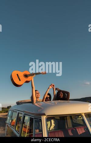 Trois jeunes filles gaies tenant de la guitare et s'amusant pendant debout dans la trappe dans le toit de la camionnette rétro dans la nature
