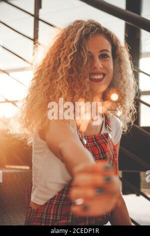 Merveilleuse jeune femme maurique souriant à l'appareil photo tout en montrant flou bâton lumineux placé dans les escaliers au soleil