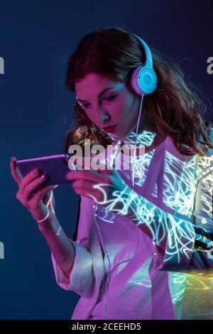 Jeune femme regardant un smartphone et portant un casque au néon lumière en studio
