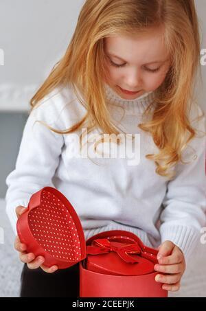 petite fille ouverture rouge présent Banque D'Images