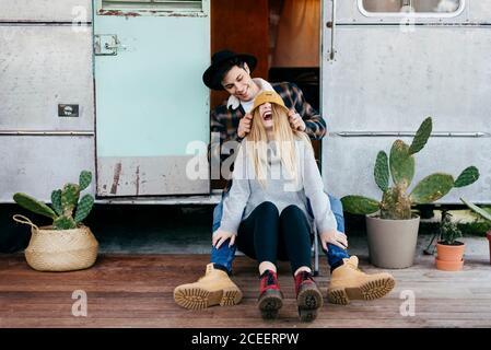Un jeune homme et une femme séduisants souriant assis près de la merde camper ensemble
