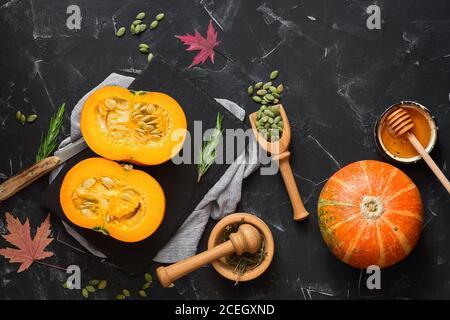 Tranché de citrouille crue avec des herbes, des graines et du miel sur fond de pierre noire. Contexte alimentaire d'automne. Thanksgiving et halloween concept de vacances. Haut vi