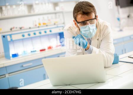 Beau jeune chercheur en blouse de laboratoire blanche et masque de protection travailler avec un ordinateur portable en étant assis dans le laboratoire