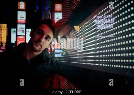 Jeune homme décontracté pendu sur un mur de verre brillant dans la rue dans la ville de nuit regardant la caméra, New York