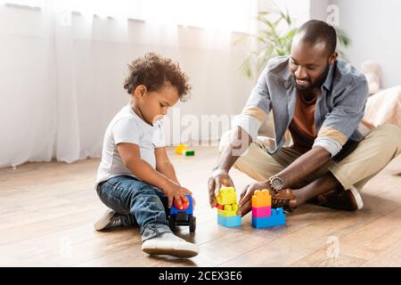 jeune afro-américain jouant avec des blocs de construction sur le sol avec petit fils Banque D'Images