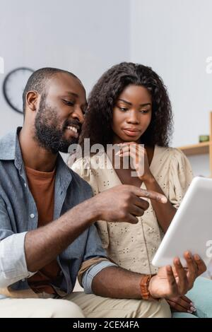 jeune afro-américain pointant du doigt vers une tablette numérique près de la femme pensive Banque D'Images