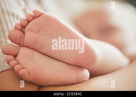 Gros plan horizontal des pieds du petit garçon caucasien, sa mère le câlin