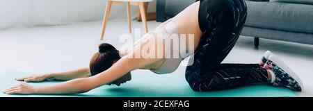 Photo panoramique de sportswoman s'étendant sur un tapis de fitness dans la vie chambre Banque D'Images