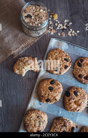 Délicieux biscuits de flocons d'avoine fraîchement cuits sur du papier de cuisson placé sur la table pendant le petit déjeuner