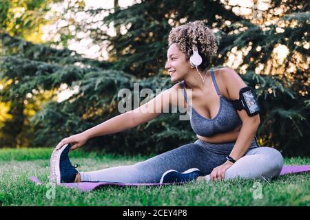 Bonne jeune femme ethnique avec des cheveux bouclés dans l'écoute de sportswear pour écouter de la musique avec un casque ou un smartphone et en étant assis vers l'avant exercice de flexion tout en étirant le corps pendant l'entraînement de fitness en été stationnement