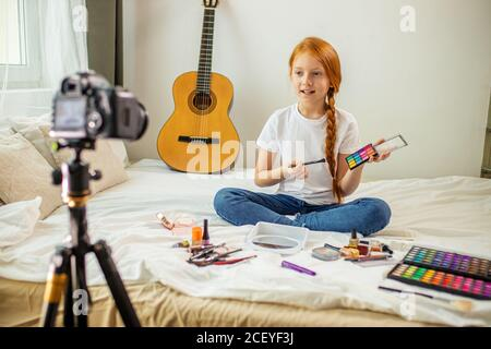 petit caucasien beauté blogger s'asseoir devant l'appareil photo, montrer de nouveaux cosmétiques décoratifs, veulent faire le maquillage, fille enregistrer vidéo sur l'appareil photo professionnel