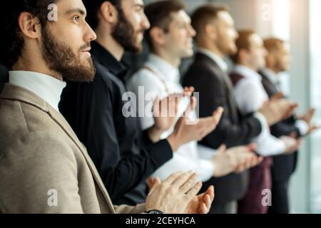 vue latérale sur un jeune groupe d'hommes d'affaires en tuxedo célébrant leur victoire, se réunissant les mains au bureau, en regardant de côté à la grande fenêtre panoramique Banque D'Images
