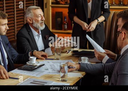 les hommes d'affaires en costume élégant s'assoient à table dans un bureau confortable discuter des plans stratégiques pour la diffusion future de différents documents dans devant