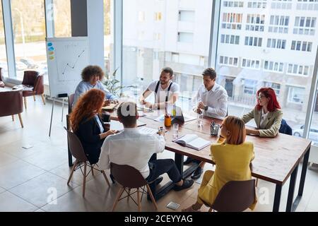 groupe d'affaires créatif et enthousiaste assis au bureau, travaillant ensemble en équipe, portant des vêtements formels. Gens d'affaires caucasiens
