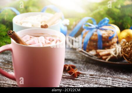 Arrière-plan de Noël de deux tasses de chocolat chaud avec guimauves, branche d'épinette et plateau avec biscuits de pain d'épice sur table en bois.