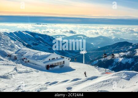 Montagnes d'hiver. Sommets enneigés et brouillard dans les vallées. Ciel bleu et rose sur la piste de ski. Remontée mécanique et bar.