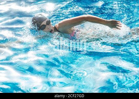 Femme avec bonnet de bain et lunettes de natation dans une piscine.