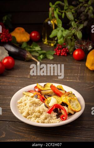 Couscous de porridge avec légumes cuits au four, courgettes et oignons, poivrons et aubergines avec épices, assiette avec nourriture sur fond de bois sombre Banque D'Images