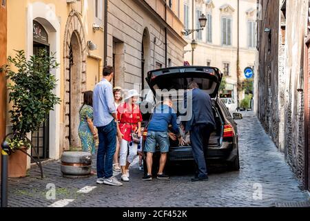 Rome, Italie - 4 septembre 2018 : rue étroite de la ville par l'hôtel HiSuiteROME avec les personnes partant du taxi sur la route et la famille sur la via di Monte Giordano Banque D'Images