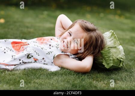 mignonne petite fille rit et couchée sur l'herbe avec le chou . enfance heureuse. Banque D'Images