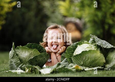 mignon petite fille a l'amusement et est couché sur l'herbe verte près des cabanes. Jolie petite fille sur le champ de chou. Concept de récolte. Enfance heureuse Banque D'Images