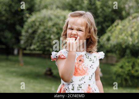 Funny kid girl eating sandwich à l'extérieur. Avoir du plaisir. En regardant la caméra. Posant sur fond nature. Alimentation saine. L'enfance. Banque D'Images