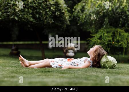 la petite fille mignonne rit et couchée sur l'herbe avec le chou . Fête des mères, famille d'amour, parentalité, concept d'enfance. Banque D'Images