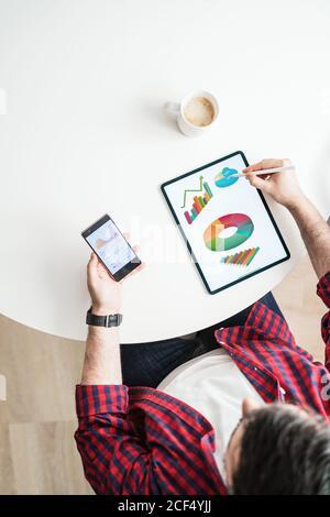 Un homme anonyme écrit sur une tablette avec des graphiques. L'homme travaille de chez lui. L'entrepreneur utilise un téléphone avec des graphiques du dessus Banque D'Images